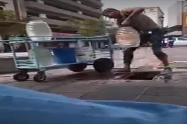 Hombre saca agua de coladera para vender aguas frescas