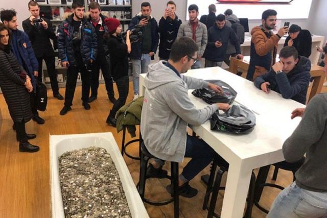 Llega con una bañera repleta de monedas para comprar un iPhone XS