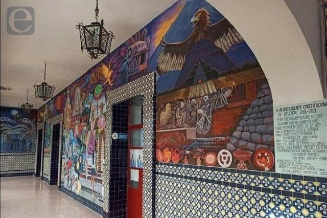 Muralista restaura el mural del palacio de Atlixco