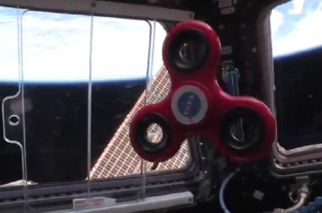 Astronautas juegan con spinner en estación espacial en gravedad cero
