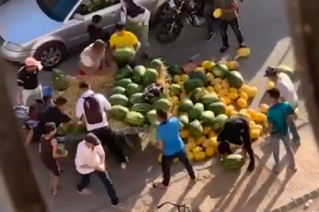 A vendedor se le cayó su fruta y las personas le ayudan a recogerla