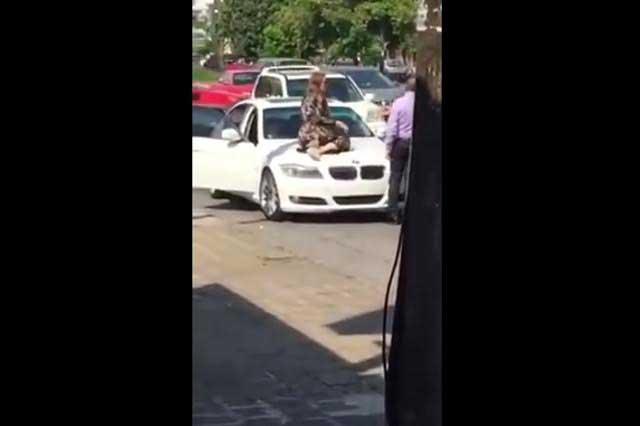 Mujer descubre a su esposo con otra en su BMW y los detiene subiéndose al cofre