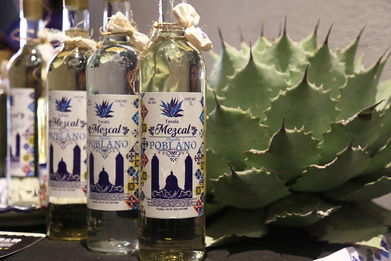 Botellas de mezcal poblano siendo exhibidas en una feria de mezcal